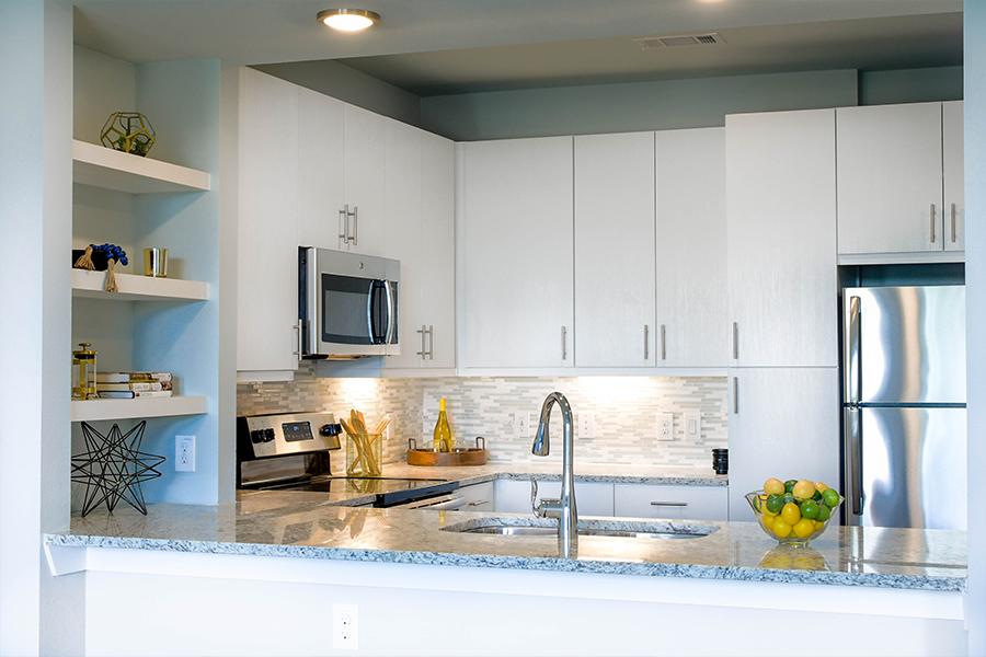 Goose-neck faucets and under-counter stainless sinks in kitchens