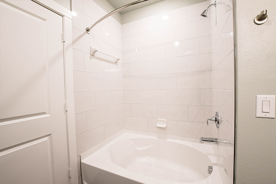 Oversized garden tub with tile surrounds available in some units + elliptical shower rods